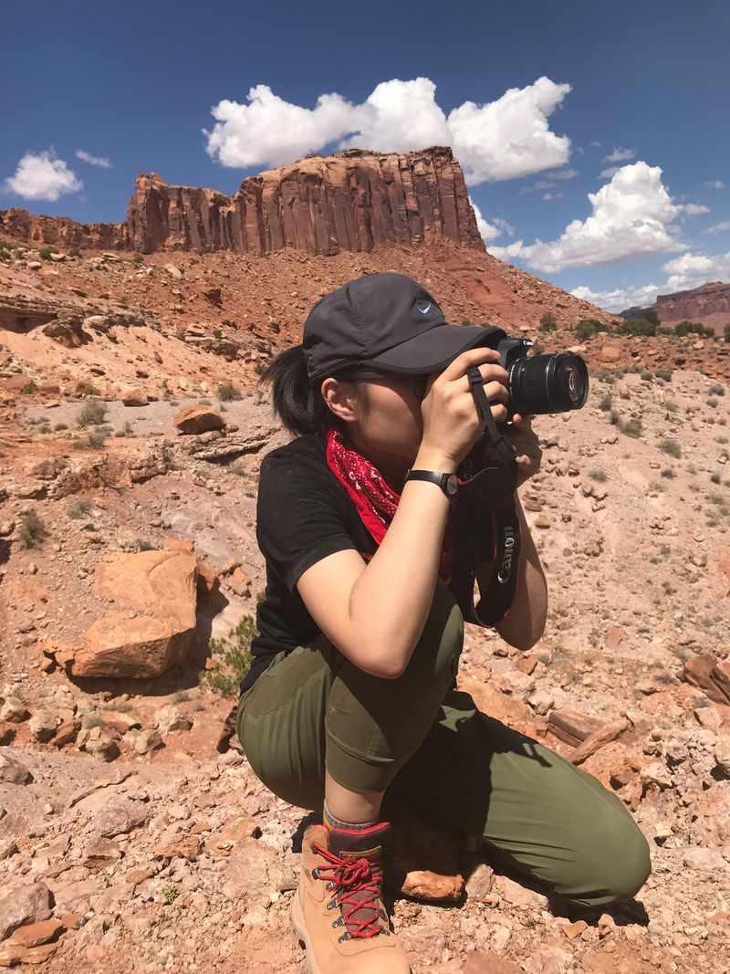 A woman in a baseball hat is kneeling and holding a camera up to her face to take a photo out in a desert landscape
