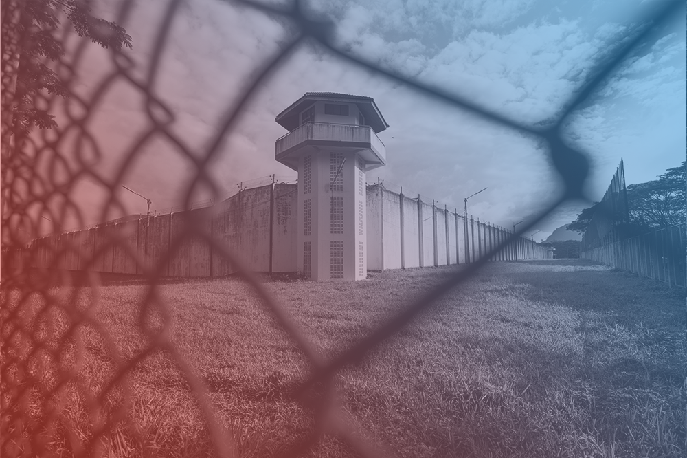 A prison tower seen through a fence. There is a blue and red filter over the image